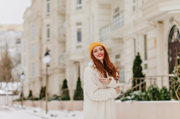 Glamouröses langhaariges mädchen, das auf unschärfestraße aufwirft. attraktives weibliches modell mit ingwerhaar, das winter genießt. Kostenlose Fotos