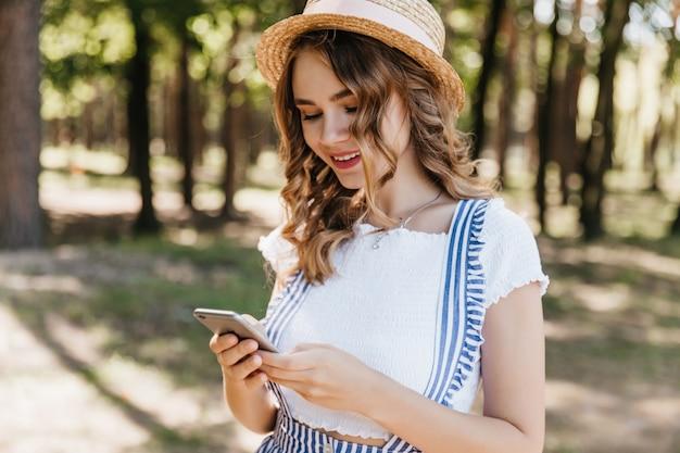 Glamouröses lockiges mädchen in den trendigen kleidern, die telefonbildschirm betrachten. außenaufnahme des faszinierenden weiblichen modells im hut sms nach dem fotoshooting im park. Kostenlose Fotos