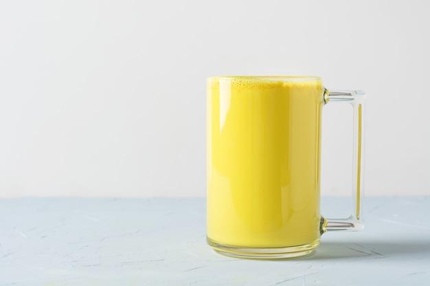 Glas ayurvedische goldene gelbwurz latte-milch mit kurkumaonweiß. Premium Fotos