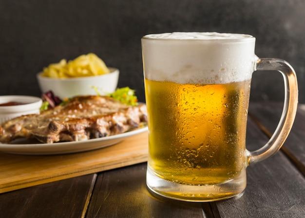 Glas bär mit steak auf teller und pommes Kostenlose Fotos
