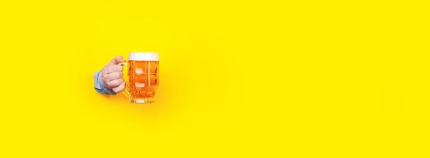 Glas bier in der hand auf gelb Premium Fotos