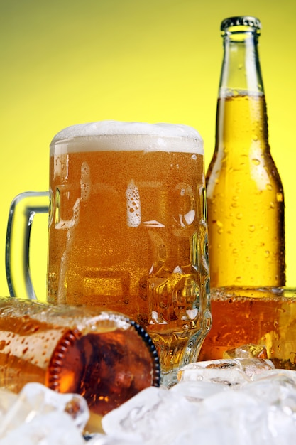 Glas bier mit schaum auf gelbem grund Kostenlose Fotos