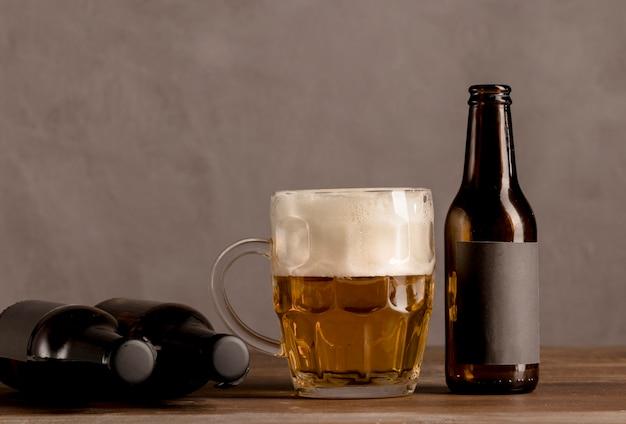 Glas bier mit schaum und braunen flaschen bier auf holztisch Kostenlose Fotos