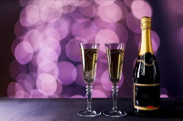 Glas champagner mit flaschen- und bokeheffekt Kostenlose Fotos