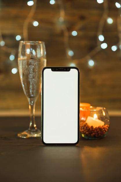 Glas champagner mit telefon auf dem tisch Kostenlose Fotos