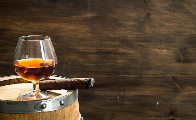 Glas cognac mit einer zigarre auf einem fass. auf einem hölzernen hintergrund. Premium Fotos