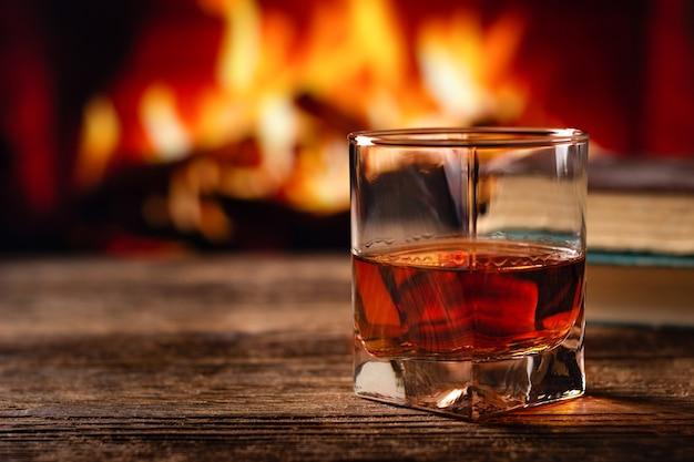 Glas cognac oder whisky. brennender kaminhintergrund verwischen. Premium Fotos