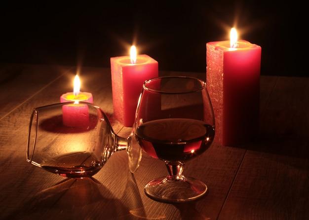 Glas des kognaks und der roten kerze auf einem holz Premium Fotos