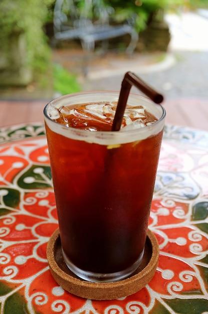 Glas eiskaffee auf der bunten tabelle an der garten-terrasse Premium Fotos