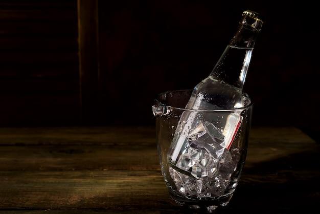 Glas-eiskübel mit einer flasche tonikum, rum oder anderem alkohol auf dunklem holz backgorund Premium Fotos