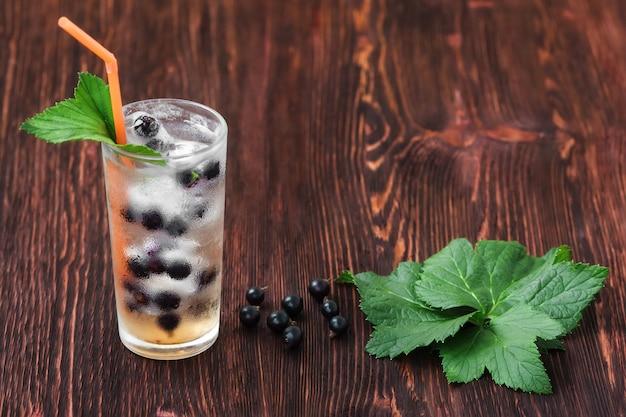 Glas frische johannisbeere mit eis, cocktail auf holztisch Premium Fotos