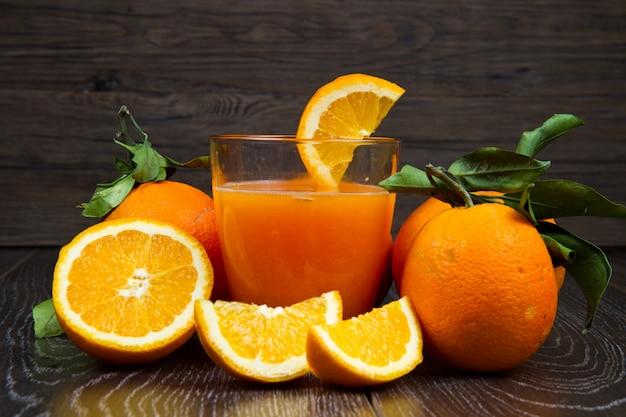 Glas frischer orangensaft und orangen auf hölzernem hintergrund Premium Fotos