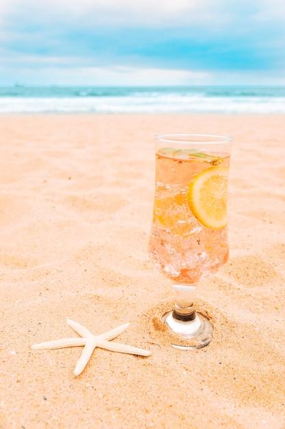 Glas frisches getränk mit geschnittenen zitrusfrüchten und starfish Kostenlose Fotos