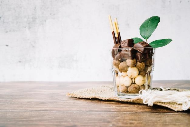 glas gef llt mit schokoladens igkeiten und stab auf. Black Bedroom Furniture Sets. Home Design Ideas