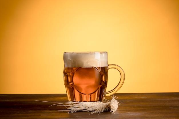 Glas helles bier mit gerstenspitze auf holztisch Premium Fotos
