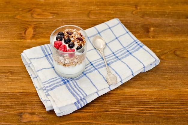 Glas joghurt mit granola und beeren auf einem holztisch. traditionelles amerikanisches frühstück Premium Fotos