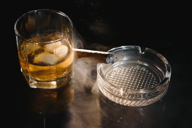 Glas kalten whisky mit zigarre auf schwarz Premium Fotos