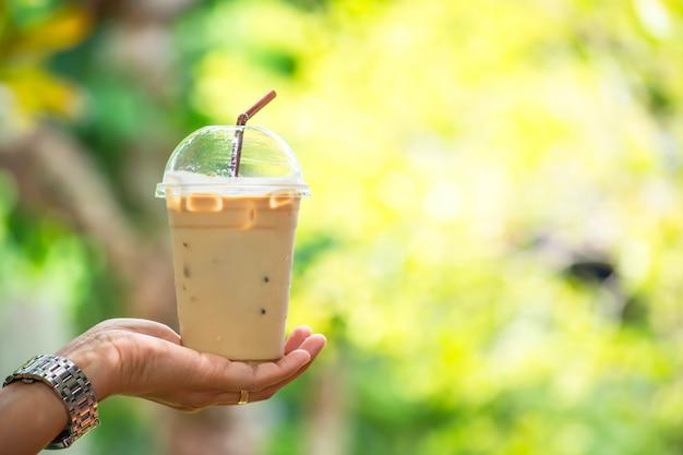 Glas kalter espressokaffee in der hand, baum der undeutlichen ansichten. Premium Fotos