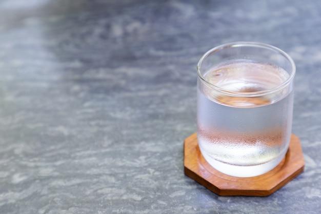 Glas kaltes wasser mit hölzernem untersetzer auf grauer steintabelle in der kaffeestube. Premium Fotos