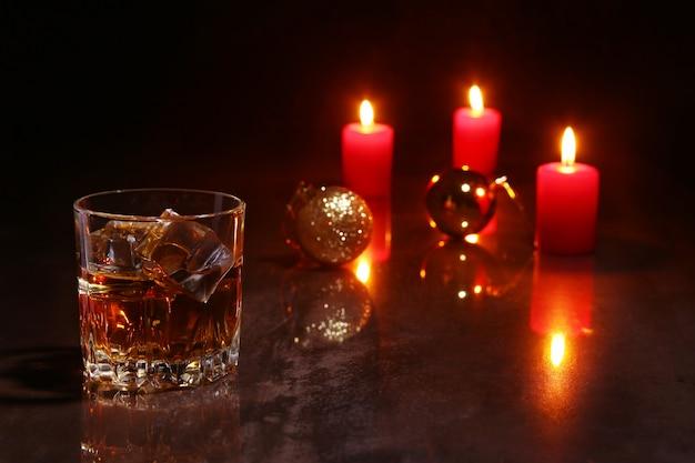 Glas kognak oder whisky, rote kerzen und bunter ball auf hölzernem Premium Fotos