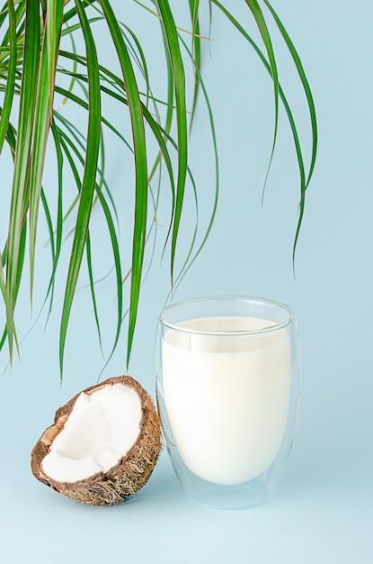 Glas kokosmilch und palmblätter auf blauer wand. vegetarisches bio-getränk. Premium Fotos