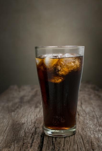 Glas kolabaum mit eiswürfeln auf hölzerner tabelle, alkoholfreies getränk. Premium Fotos