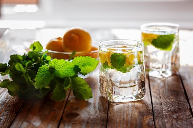 Glas limonade mit frischer zitrone und minze auf hölzernem hintergrund Premium Fotos