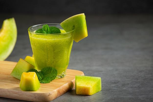 Glas melonensaft auf holzschneidebrett setzen Kostenlose Fotos