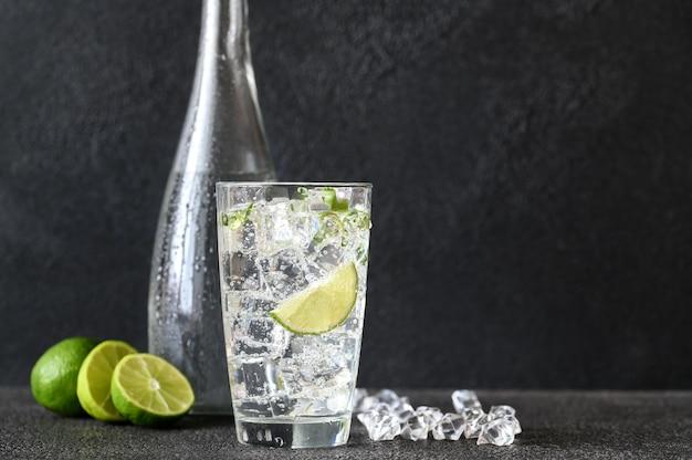 Glas mineralwasser mit eiswürfeln und limettenscheibe Premium Fotos
