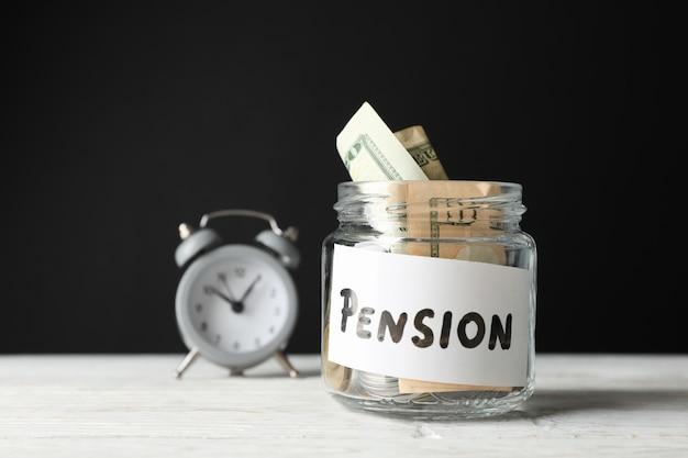 Glas mit geld und wecker gegen schwarz, nahaufnahme Premium Fotos