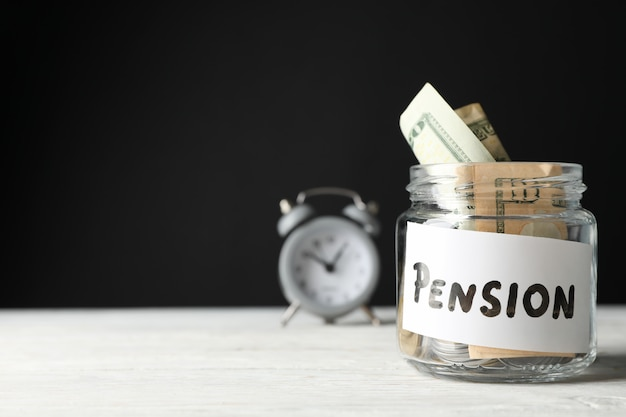 Glas mit geld und wecker gegen schwarze oberfläche Premium Fotos