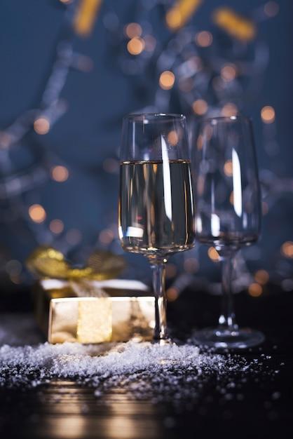 Glas mit getränk an bord in der nähe von ornament schnee und präsentkarton Kostenlose Fotos