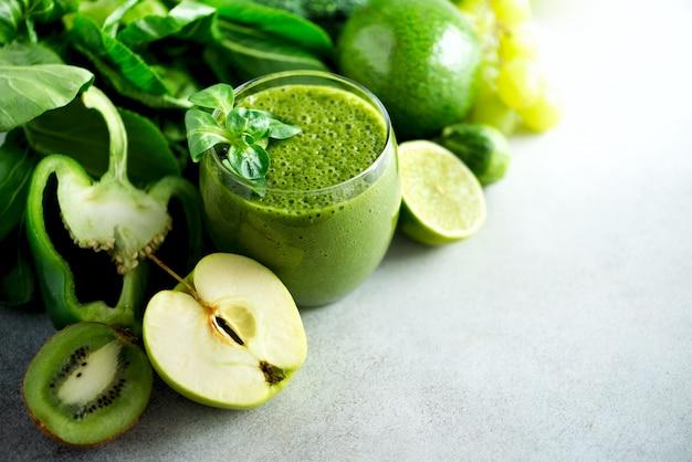 Glas mit grünem gesundheitssmoothie, kohlblättern, kalk, apfel, kiwi, trauben, banane, avocado, kopfsalat. rohes, veganes, vegetarisches, alkalisches nahrungsmittelkonzept. Premium Fotos