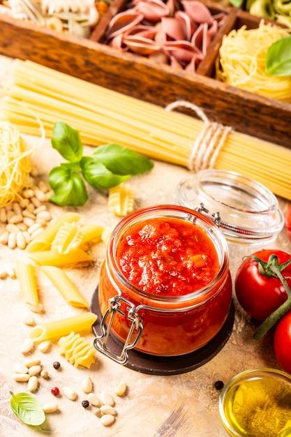 Glas mit hausgemachten klassischen würzigen tomatenteigwaren oder pizzasoße. Premium Fotos