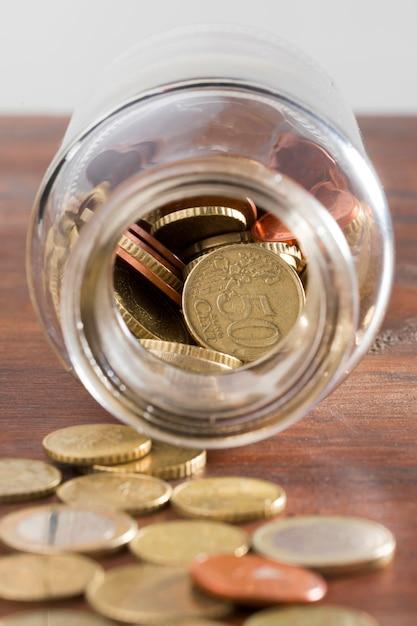 Glas mit münzen auf dem tisch Kostenlose Fotos
