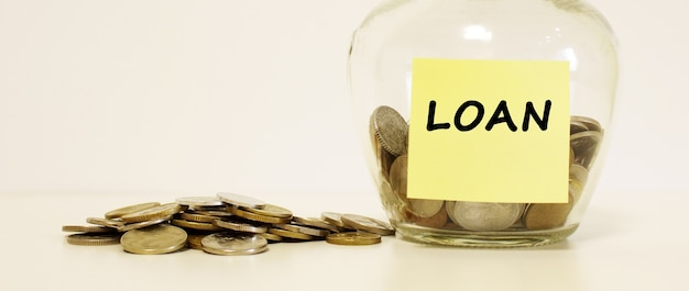 Glas mit münzen zum sparen. die inschrift auf dem briefpapier darlehen. finanzkonzept. Premium Fotos