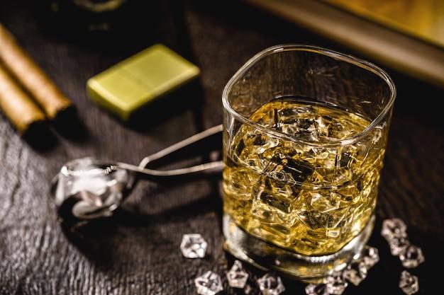 Glas mit whisky und eiszange auf holztisch Premium Fotos