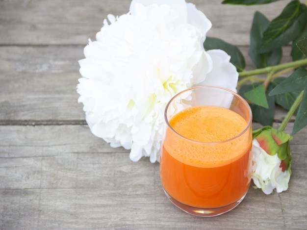 Glas orange karottensaft auf holz freier exemplarplatz. Premium Fotos