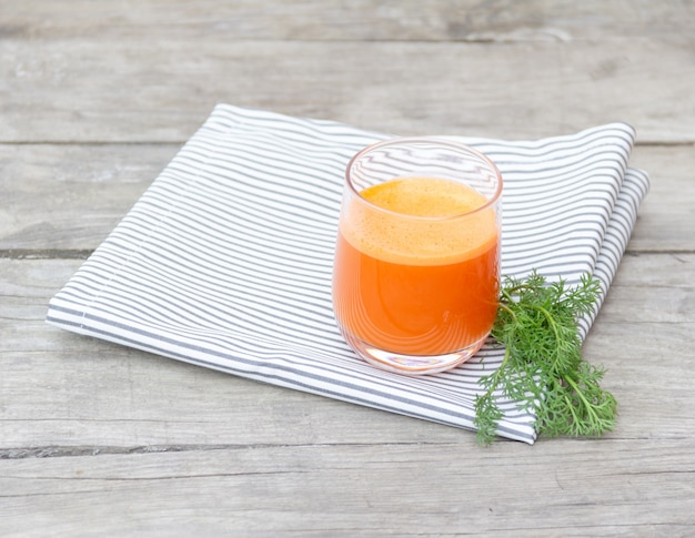 Glas orange karottensaft auf serviette auf holz Premium Fotos