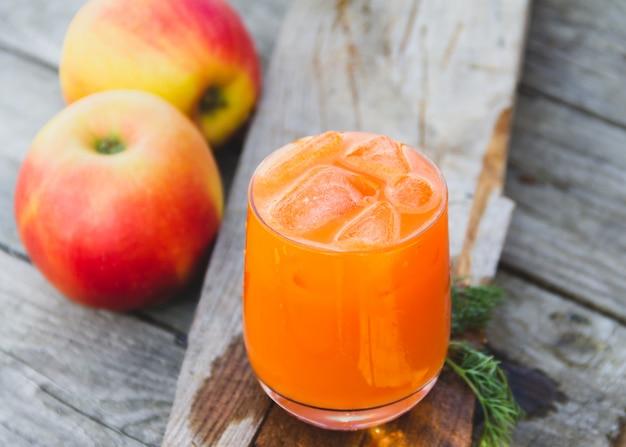 Glas orange karottensaft mit äpfeln auf holz Premium Fotos