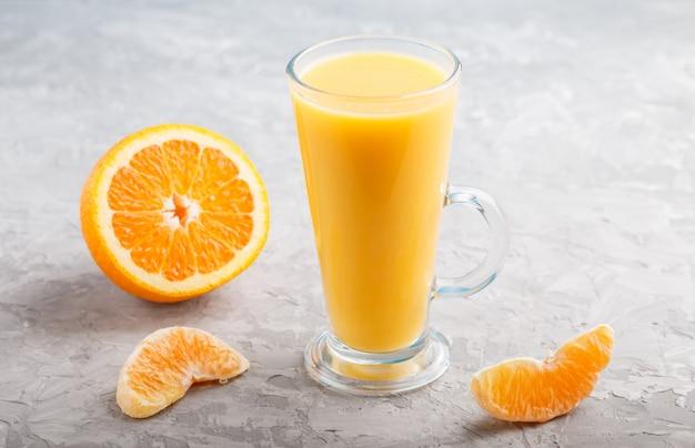Glas orangensaft auf einem grauen konkreten hintergrund Premium Fotos