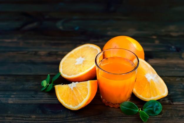 Glas orangensaft und eine gruppe orangen auf dunklem brett Premium Fotos