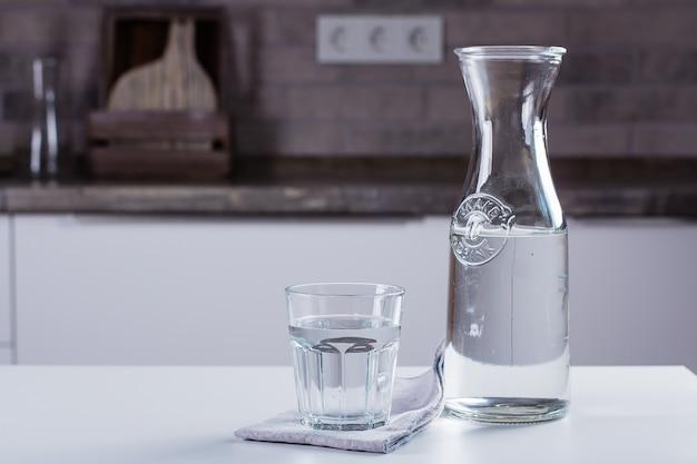 Glas reines wasser und flasche auf küchentisch. sauberes konzept Premium Fotos