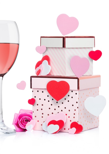 Glas rosa wein mit herzen und rosa geschenkbox und stieg für valentinstag auf weißem hintergrund mit fliegenherzen Premium Fotos