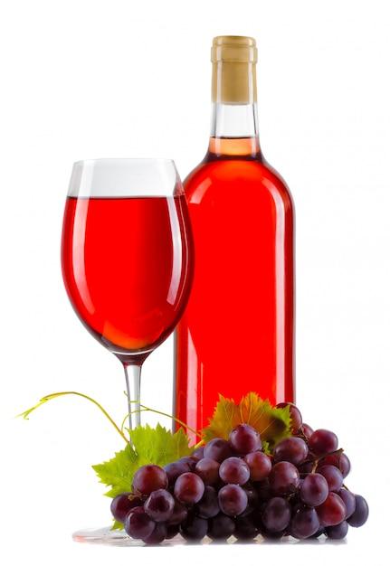 Glas rosafarbener wein mit der flasche und reifen trauben getrennt Premium Fotos