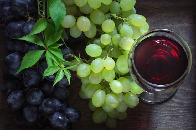 Glas rotwein mit reifer traube auf hölzernem brett. Premium Fotos