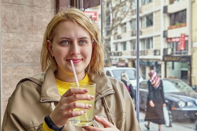 Glas saft mit strohhalm in den händen der schönen jungen kaukasischen frau, die durch fenster innerhalb des cafés mit blick auf die straße sitzt. Premium Fotos