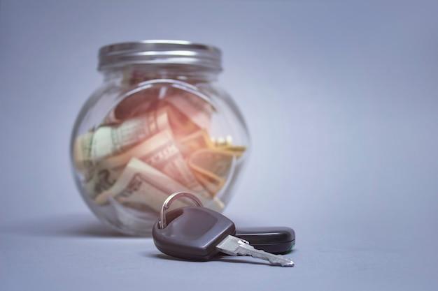 Glas sparschwein mit dollars und autoschlüsseln an einer hellen wand mit glänzendem effekt. geld beiseite gelegt, um ein auto zu kaufen. Premium Fotos