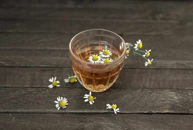 Glas-teetasse mit kamille auf einem hölzernen hintergrund. kamillenblüten sind verstreut. Premium Fotos