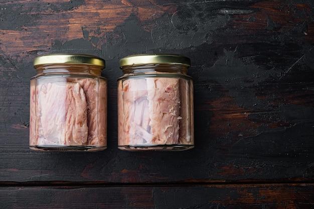 Glas thunfischfilet in olivenöl auf altem holztisch, draufsicht Premium Fotos